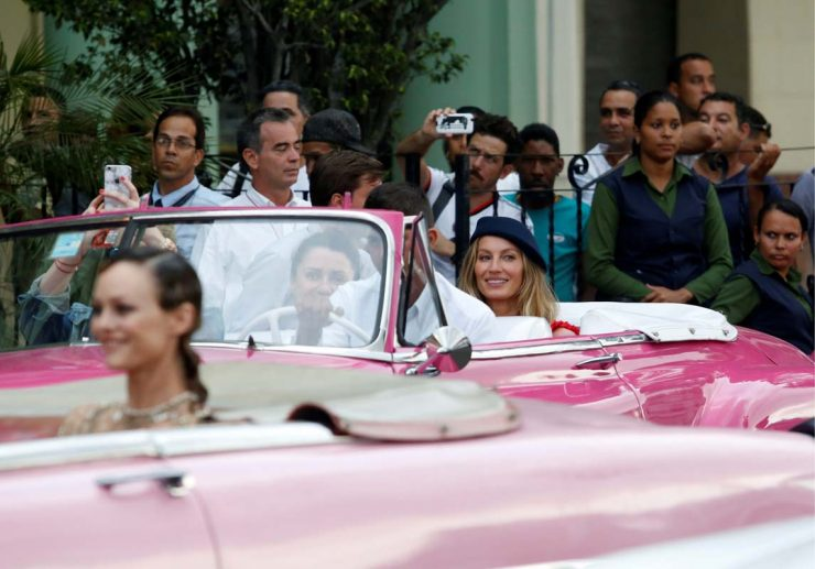 Brazilian supermodel Gisele Bundchen (R, blue hat) rides in a vintage car to attend a fashion show by Chanel, the first major fashion house to send models down the catwalk in Cuba, in Havana, May 3, 2016. REUTERS/Stringer  EDITORIAL USE ONLY. NO RESALES. NO ARCHIVECODE: X80002